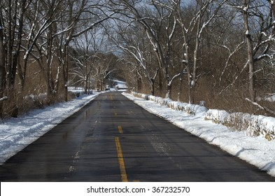 Beautiful winter scene with a rural country road recently plowed clear of snow with frosty trees along both sides.