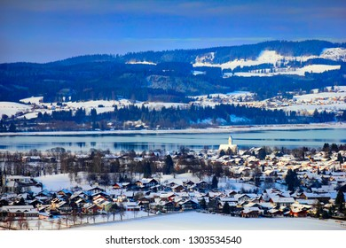 Beautiful winter scenery, hills, wood, lake, little country houses and white church covered with snow. Waltenhofen and Schwangau village, view from Neuschwanstein castle, Bayern, Germany, Europe