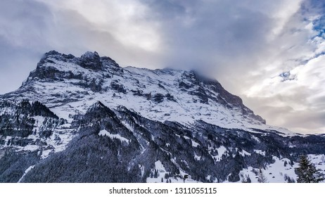 beautiful winter scenery in the swiss alps with a mountain covered in clouds