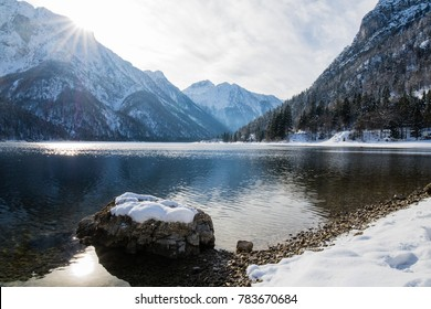 beautiful winter snowy scenery reflection on lake lago del predil with isolated snowy rock in julian alps, italy