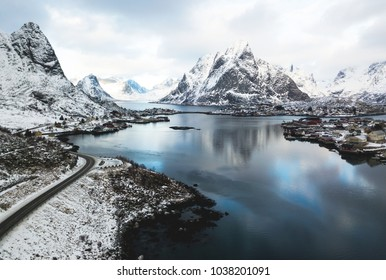 Beautiful winter snowy wide-angle summer aerial view of Reine, Norway, Lofoten Islands, with skyline, mountains, famous fishing village with red fishing cabins, Moskenesoya, Nordland, shot from drone