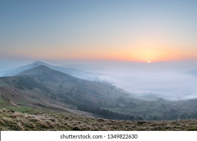 Beautiful Winter sunrise landscape image of The Great Ridge in the Peak District in England with a cloud inversion and mist in the Hope Valley with a lovely orange glow