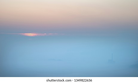 Beautiful Winter sunrise landscape image of The Hope Valley in the Peak District in England with a cloud inversion and mist