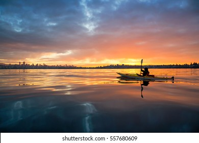 Beautiful winter sunrise on the water with a man on the ocean kayak going towards Vancouver Downtown, BC, Canada.