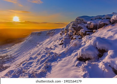 Beautiful winter sunrise over a snow covered mountain in the Brecon Beacons, Wales