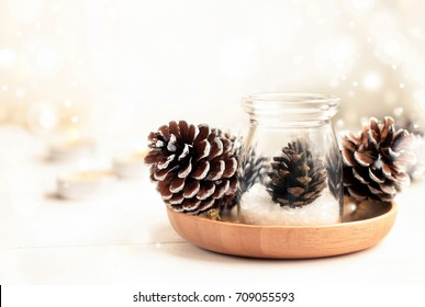 Beautiful winter time home natural decor with sparkling bokeh background. Pine cones in glass jar and candles on table, copy space. Dreamy light and soft focus.