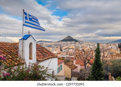 Beautiful winter view on Lycabettus hill and small church with Greece flag from Plaka, Athens