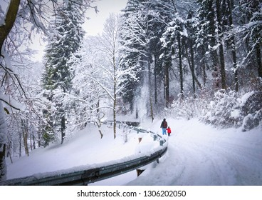 Beautiful winter view, snowy weather, couple of people (dad and daughter) holding hands walking on snow covered road in Innsbruck, Tyrol (Tirol), western Austria, Europe