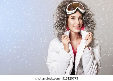 Beautiful Winter Woman in Winter Clothes. Woman smile wears a warm winter white jacket with a hood on her head and glasses for snowboarding