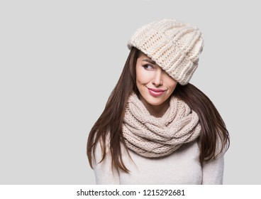 Beautiful winter woman portrait. Smiling girl wearing warm clothes looking away. Isolated on grey background