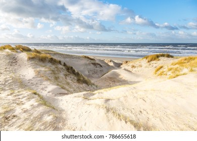 Beautiful winters dune scenery along Dutch North Sea coast with by wind power carved   deep holes and valleys with steep walls against a background with wild waves  and a blue sky  with clouds