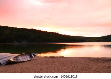 Beautiful Wisconsin nature background. Scenic view with boats on a lake beach during sunset. Devils Lake State Park south shore, Baraboo area, Wisconsin, Midwest USA.