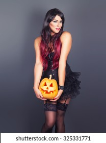 Beautiful witch in black gothic Halloween costume holding Jack-o-lantern in hands