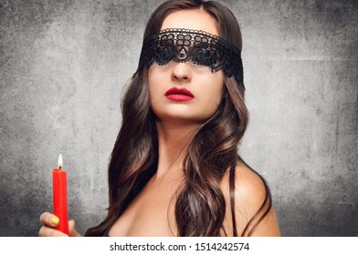 A beautiful witch in a black lace mask holds an old book and a red candle in her hands.