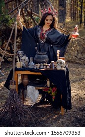 Beautiful witch in black, long dress, with red crown in her long hair. Posing in pine forest. Spells, magic and witchcraft. Full length portrait.