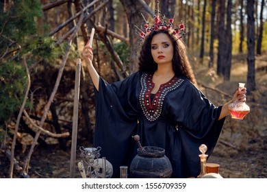 Beautiful witch in black, long dress, with red crown in her long, curly hair. Posing in pine forest. Spells, magic and witchcraft. Close-up.