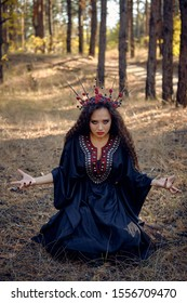 Beautiful witch in black, long dress, with red crown in her long hair. Posing sitting in pine forest. Spells, magic and witchcraft. Full length.