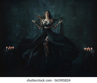 Beautiful witch floating in the air. Background dark room. Girl dressed in a black dress with a long train. Creative color.