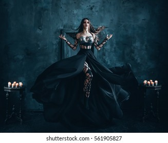 Beautiful witch floating in the air. Background dark room with a cold moonlight.. Girl dressed in a black dress with a long train. Creative color.