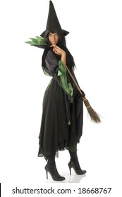 beautiful witch with hat and broom in black and green dress