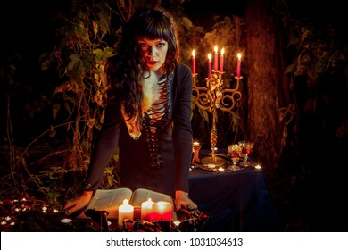 Beautiful witch with the vintage book of magic invites you into the forest.