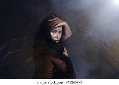 Beautiful Witchcraft Asian woman in scary Witch snow ghost story look nake shoulders, studio lighting dark background wood branch stick