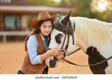 Beautiful womam sensuality elegance woman cowgirl on during sunset, riding a horse. Clothed blue jeans,Has slim sport body. Portrait nature. People and animals. Equestrian. vintage style