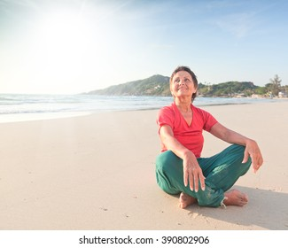 beautiful woman 50 years sitting on the beach after yoga