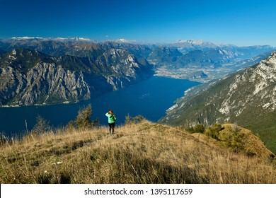 A beautiful woman admiring the beautiful Lake Garda from Monte Baldo, Panorama of the gorgeous Garda lake surrounded by mountains