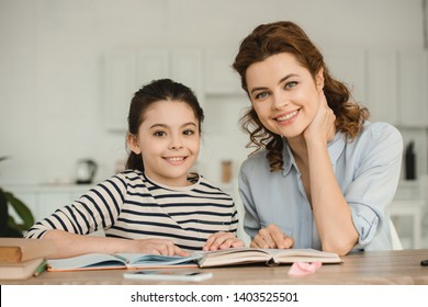 beautiful woman with adorable smiling daughter looking at camera while doing homework together
