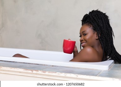 Beautiful woman with afro hair dreaming in bath tub