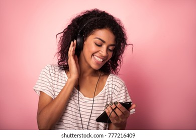 Beautiful woman with afro hair listining to music and dancing on