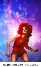 Beautiful woman with afro haircut is dancing disco. Photo with blurred effects.