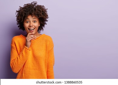 Beautiful woman with Afro hairstyle smiles gently at camera, touches chin, looks happily at camera, wears orange jumper, isolated over purple background with copy space aside for your promotion