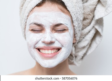 beautiful woman after shower with a towel on her head smiling cream on face.