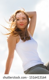 Beautiful woman against white sky. Female during spring weather, having long brown hair wind tousled windblowed.