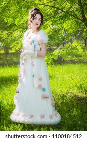 Beautiful woman in an antique bride dress with a book in her hands in a spring garden for a walk.