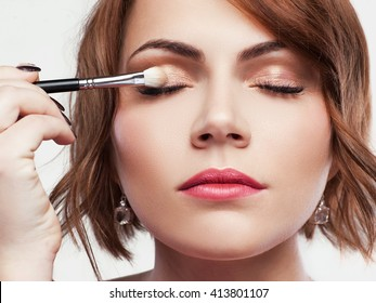 Beautiful woman applies golden natural colored eyeshadow with make up brush. Nude eye makeup closeup. Headshot of girl applies shiny  brown eyeshadow