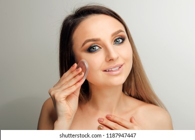 Beautiful Woman applying bb cream with Silicone Sponge.