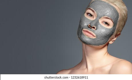 Beautiful Woman Applying Black Facial Mask. Beauty Treatments. Close-up Portrait of Spa Girl Apply Clay Facial mask on grey background.