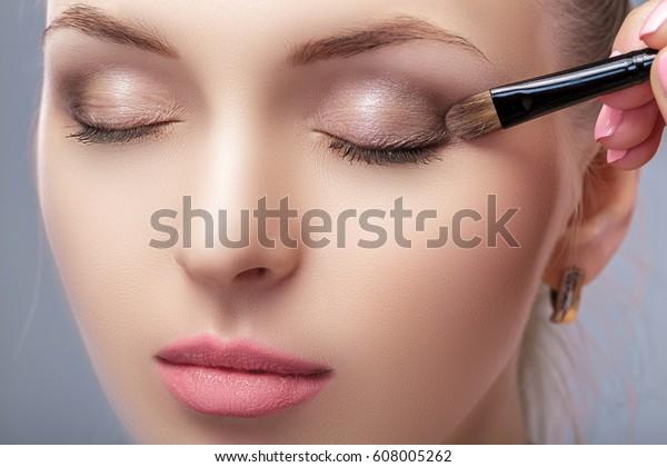 beautiful woman applying brown eye shadow using makeup brush. makeup for blue eyes