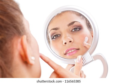 Beautiful woman applying cream on face
