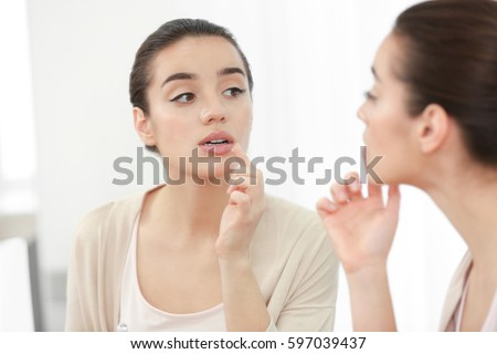 Beautiful woman applying cream onto lips near mirror
