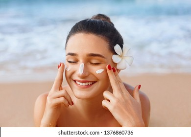 Beautiful woman applying cream sunscreen on a tanned face. Sunscreen. Skin and body care. The girl uses a sunscreen for her skin. Portrait of a female holding suntan lotion and moisturizing sunscreen.
