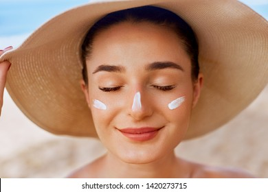 Beautiful woman applying cream sunscreen on tanned face. Sunscreen. Skin and body care. The girl uses a sunscreen for her skin. Portrait of a female holding suntan lotion and moisturizing sunscreen.