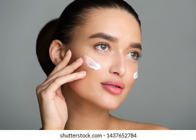 Beautiful Woman Applying Face Cream and Looking Away, Grey Studio Background
