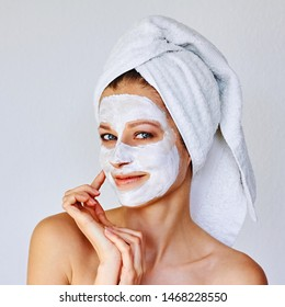 Beautiful woman applying facial mask on her face. Skin care and treatment, spa, natural beauty and cosmetology concept