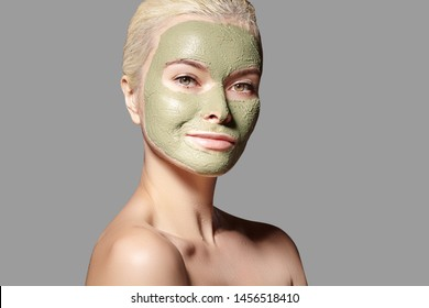 Beautiful Woman Applying Green Facial Mask. Beauty Treatments. Close-up Portrait of Spa Girl Apply Clay Facial mask on grey background.