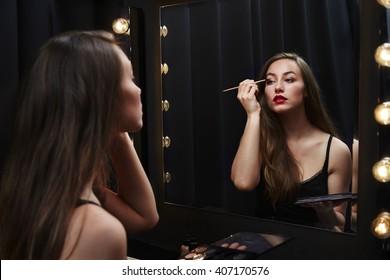Beautiful woman applying make up in mirror