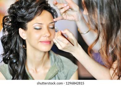 Beautiful woman applying makeup by professional makeup artist